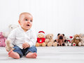 Barefoot baby on white background with cuddly toys cute little boy Stock Photo