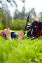 Barefoot biker enjoying relaxation lying in fresh green grass outdoors summer sunny park Royalty Free Stock Photos