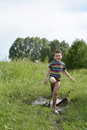 Barefoot boy runs through a puddle summer field near dirty running splashing everywhere Stock Image