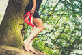 Barefoot brunette girl in black dress outdoor with red high heels her hands Stock Photo