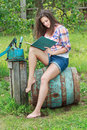 Barefoot brunette girl sitting on old vintage blue wooden barrel with book in summer garden Royalty Free Stock Photo