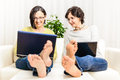 Barefoot funny happy women chat browsing home laptop brunette adult on sofa at living room using personal computer or internet Stock Image