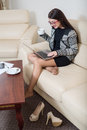 Barefoot girl sitting on couch Royalty Free Stock Photo