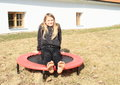Barefoot girl sitting on trampoline Royalty Free Stock Photo