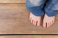 Barefoot girl standing on wooden floor close up from above Royalty Free Stock Images