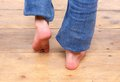 Barefoot girl walking on wooden floor close up Stock Photo