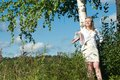 Barefoot in the grass young woman standing at birch trunk Royalty Free Stock Image