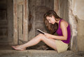 Barefoot reading on a porch young woman book an old derelict Royalty Free Stock Images