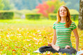 Barefoot red-haired girl practicing yoga in the park Royalty Free Stock Photo
