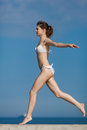 Barefoot slim girl in white bikini running jogging along the beach Royalty Free Stock Photos