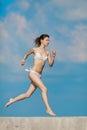 Barefoot slim girl in white bikini running outdoors Royalty Free Stock Photo