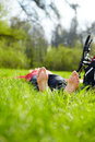 Barefoot tourist enjoying relaxation lying in fresh green grass outdoors summer sunny park Stock Photos