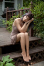 Barefoot woman on porch an image of a pretty sitting a wooden in a dress and bare feet Stock Photography