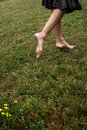 Barefoot woman walking on the grass Stock Photo