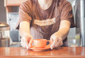 Barista offering mini orange cup of coffee stock photo Royalty Free Stock Image