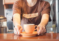 Barista offering orange cup of coffee stock photo Royalty Free Stock Photography