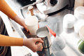 Barista steaming milk churns for cappuccino, coffee machine, selective focus