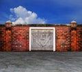Bark panel  wood barn door on old brick wall with blue sky behin Royalty Free Stock Photo