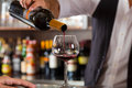 Barkeeper pouring red wine in glass on bar in restaurant or hotel Royalty Free Stock Images