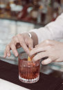 Barman is decorating drink with lemon zest toned Royalty Free Stock Image