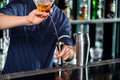 Barman makes cocktail on the counter accessories bartender pouring alcohol to steel jigger with shaker standing nearby a bar Royalty Free Stock Photos