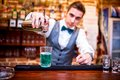 Barman pouring a cocktail drink and looking at camera Royalty Free Stock Photo