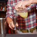 Barman is pouring orange jucie in jigger a Stock Photos