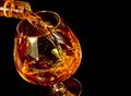 Barman pouring snifter of brandy in elegant typical cognac glass on black background Royalty Free Stock Photo