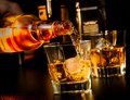 Barman pouring whiskey in front of whiskey glass and bottles on wood table Royalty Free Stock Images