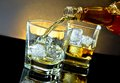 Barman pouring whiskey in front of whiskey glass on warm light Royalty Free Stock Photo