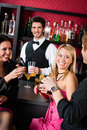 Barman prepare cocktails friends drinking at bar Stock Image