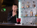 Barman serving a customer in nightclub looking round attentively as someone places an order for drink Stock Photo