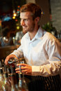 Barman serving drinks in nightclub smiling Royalty Free Stock Image