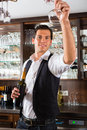 Barman standing behind bar in restaurant reaching for a wineglass Stock Photo