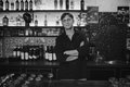 Barman at work in the pub with crossed arms black and white photo Stock Photo