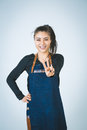 Barmen a shoot of young caucasian woman in apron as a showing the sign victory two fingers up Stock Photo