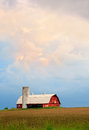 Barn and evening sky a dramatic sunset hangs over a red with silo basketball hoop in the midwestern united states Royalty Free Stock Image