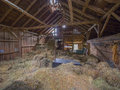 Barn interior old post and beam with hay on the floor Stock Photography