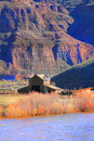 Barn on river a ranch with a sits the banks of the john day at the bottom of steep canyon hills Royalty Free Stock Image