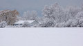 Barn in the snow sits at edge of a covered field nestled between snowy trees Stock Photos