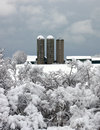 Barn in the snow three silos against a grey sky on a snowy morning Stock Photo