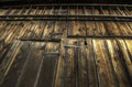 Barn wood side of weathered brown wooden with metal latches and a horizontal wooden ladder at the top Stock Images