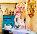 Baroque fashion blonde housewife woman iron chores Royalty Free Stock Image