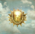 Baroque sun artistic imagine of a sculpture of representing the in the cloudy sky in the background Stock Images