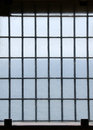 Barred prison window with ocean view Stock Image