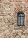 Barred window in stone wall Royalty Free Stock Image