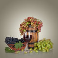 Barrel bottles grapes and glass of wine on gray background Royalty Free Stock Images
