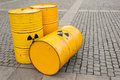 Barrels of biohazard three yellow metal with symbols on a cobblestone road Royalty Free Stock Photos