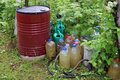 Barrels, canisters and watering cans with water Royalty Free Stock Photo