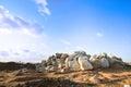 Barren landscape with hill of rock boulder stone blue sky Stock Photos